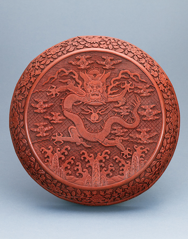 A RED LACQUER BOX, carved with design of dragon riding the waves